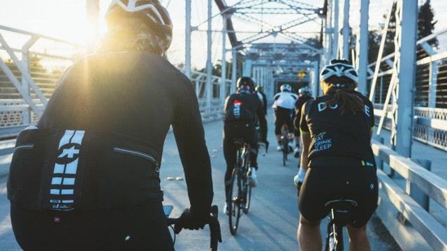 Gruppe von Radfahrern überquert in Zweierreihe eine Brücke