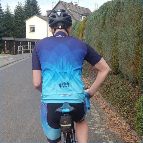 Radfahrer signalisiert mit ausgefahrenem Ellenbogen, dass er überholt werden möchte