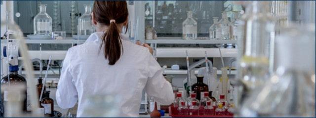 Ärztin mit weißem Kittel arbeitet mit Reagenzgläsern
