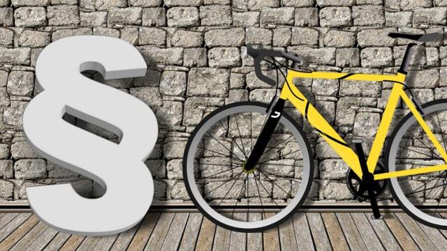 Rennrad lehnt an einer Wand neben einem Paragraphen.