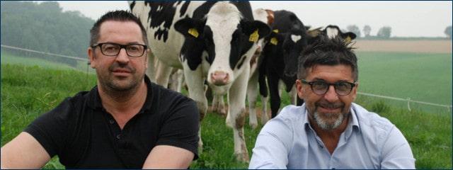 Die beiden Remor Brüder sitzen auf einer Weide. Mehrere Kühe sind im Hintergrund.